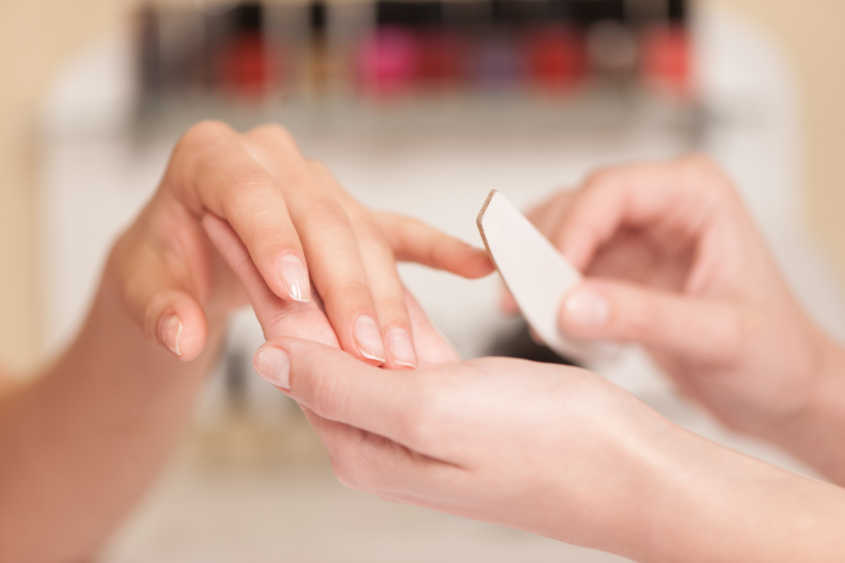 Woman in nail salon receiving manicure.