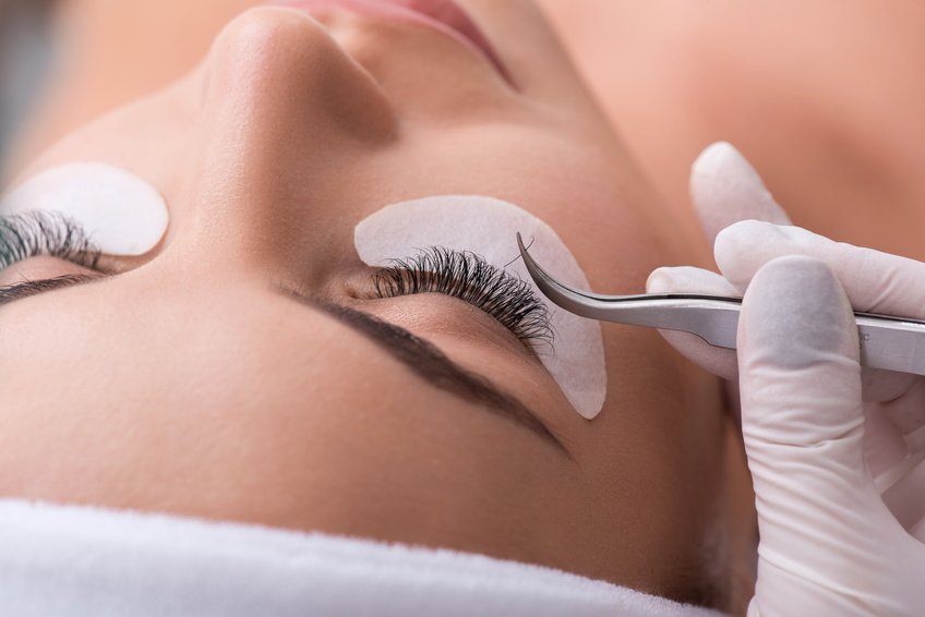 Skillful cosmetician making artificial eyelashes